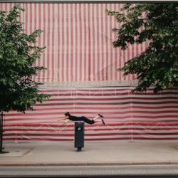 Woman balancing on meter in front of striped wall