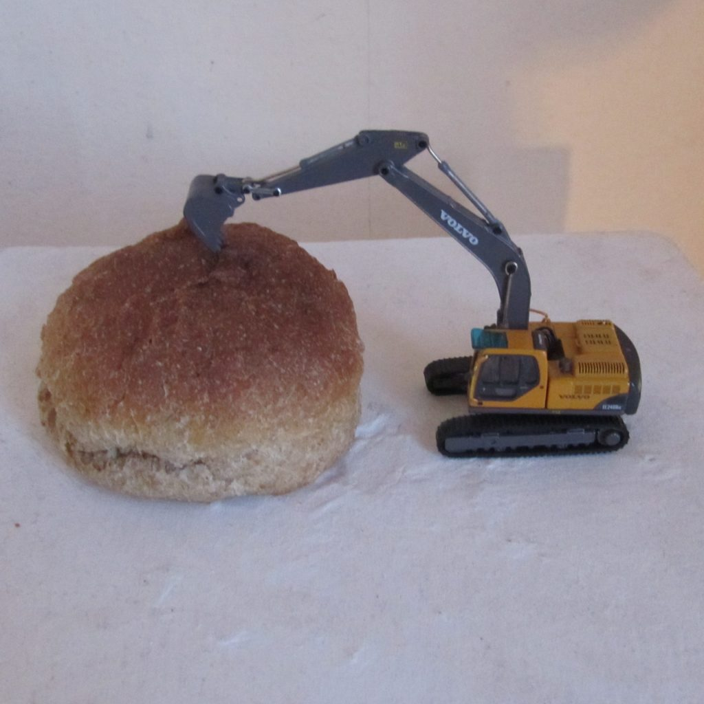 Toy digger working on a bread roll