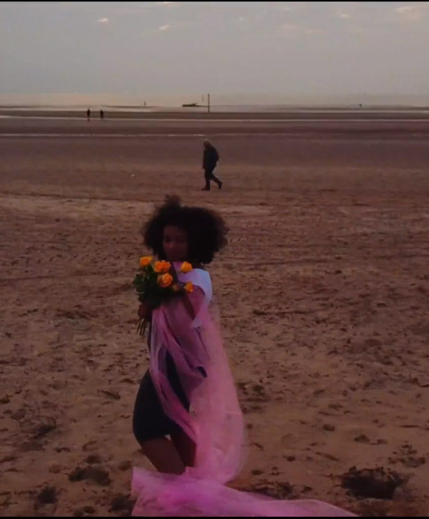 woman standing on a beach wrapped in pink fabric and holding yellow flowers