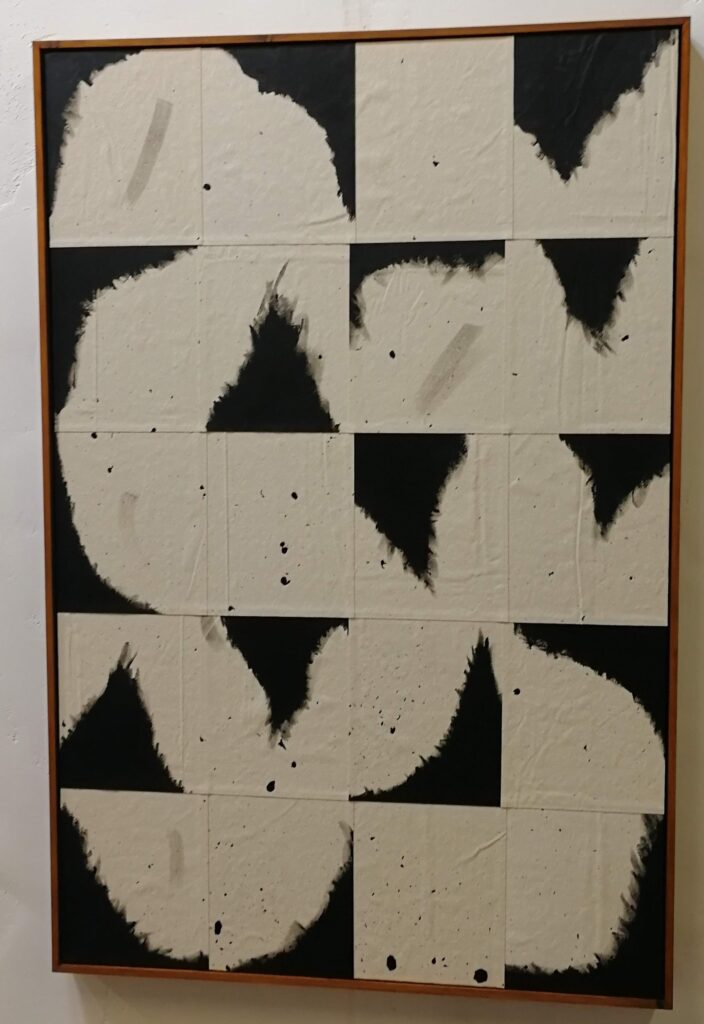 A series of black and white panels with abstract shapes to create one large work, most shapes seem to be based on triangles