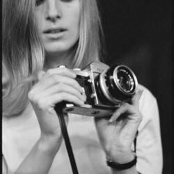Black & white photo of Linda McCartney holding a camera