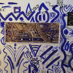 Gold Maria Akanbi artwork, a white wall painted with blue patterns, with stand-alone artworks in black and gold.