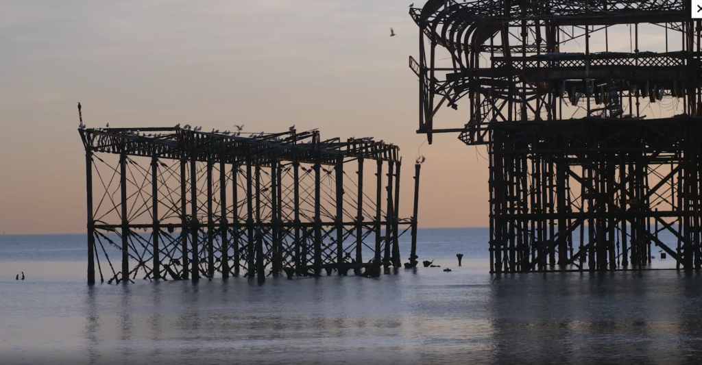 Film still of a burned-out pier building where structure is down to the bones. It's black and in the sea, which is blue and calm, and reflecting the sky which is dusky orange.