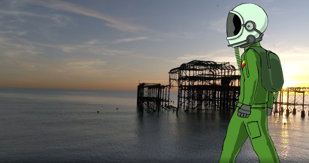 Film still of a sea with a burned-out pier building sitting on the right. Animated over this is an astronaut in a green suit walking from right-left side of screen.