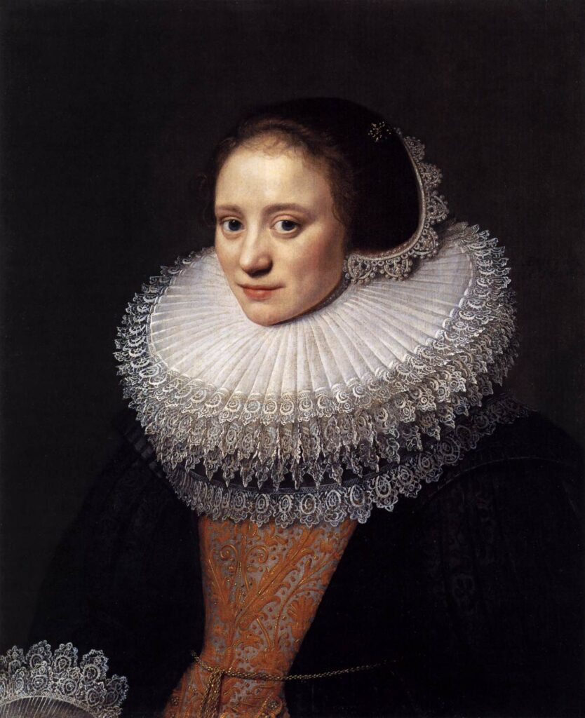 A woman in at least 4 layers of ruff trimmed with lace, in a dark dress and headgear.