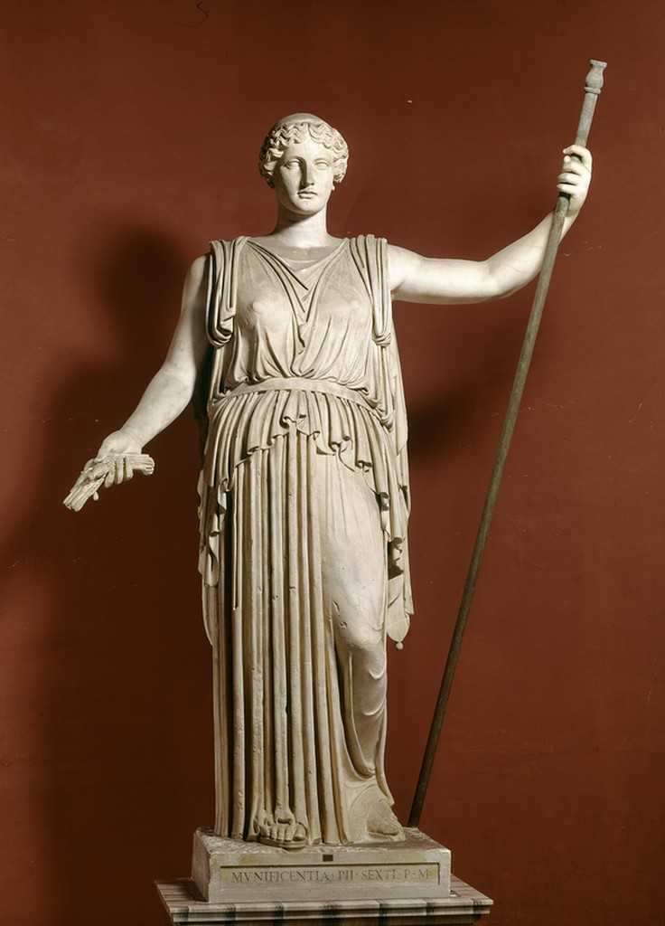 A sculpture of Demeter, corn in one hand and staff in another, in a broad hanging outfit