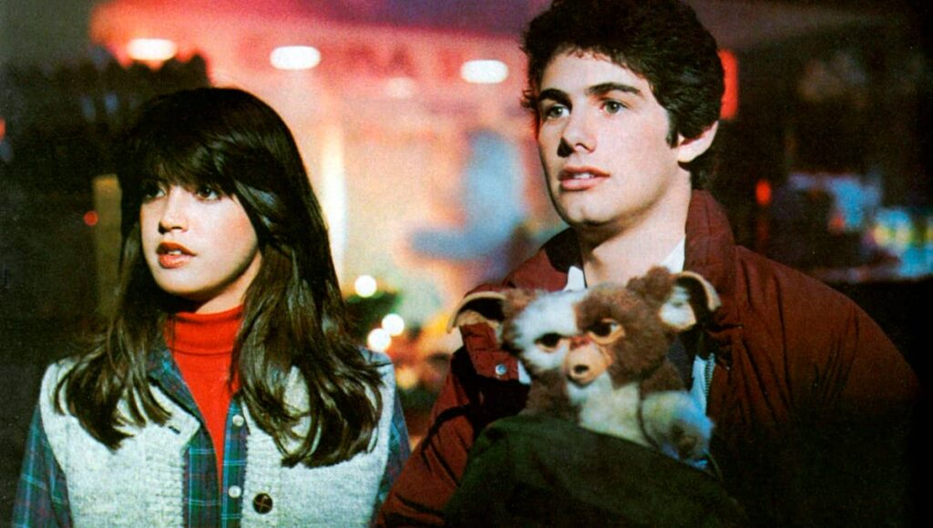 A young man with brown hair in a red jacket; a young woman with thick brown hair in a light jacket, the boy is holding a fluffy creature with white and brown fur