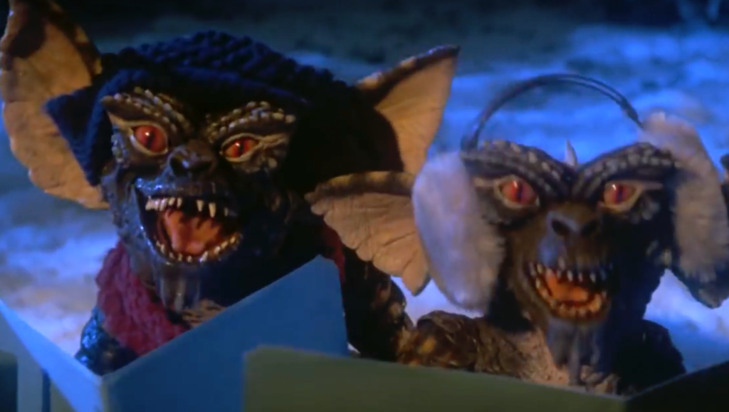 Two Gremlins (small scaly monsters with sharp teeth, red eyes and pointy ears) wearing hats and earmuffs carol singing in the snow