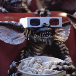a gremlin - a scaly creature with sharp teeth and large ears - in a cinema wearing 3d glasses and holding a large box of popcorn