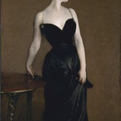 woman in a black low-cut dress with chain shoulder straps, a very cinched in waist, all in black with very pale while skin.