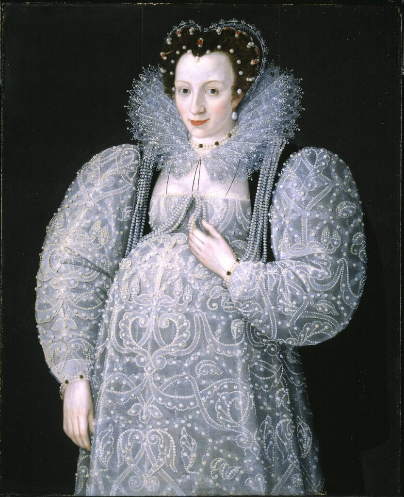 A woman in a white, finely decorated dress, pregnant and smiling.