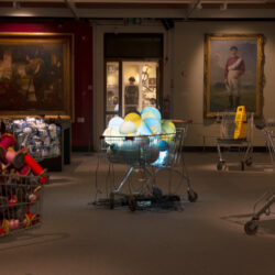 An art gallery space with paintings on the wall and five shopping trolleys in the space. On the left one is filled with thread bobbins, one with sugar bags. On the right one is filled with atlases, one with a bucket and wet floor sign. The central one is filled with plastic globes which are each lit from inside and are glowing. Copyright Warrington Museum & Art Gallery