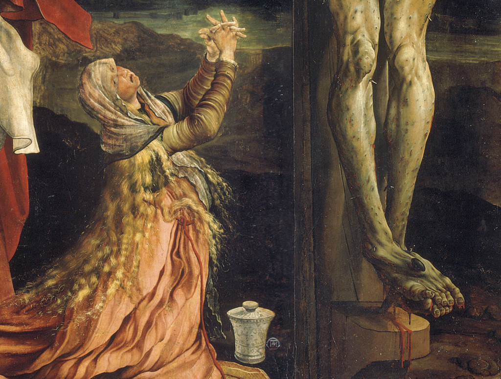 A woman with long blonde hair in a pink dress kneels by the foot of Christ's cross. Jesus' legs and feet are green, mottled, bleeding like they're very ill indeed.