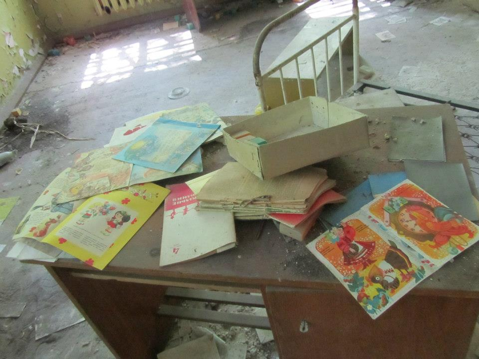 A desk covered in children's books. The site has long been abandoned and everything is covered in dirt and dust.