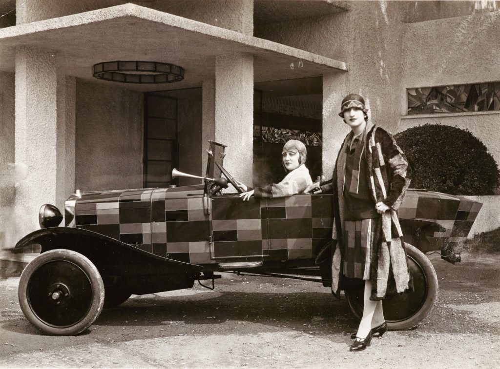 A black and white photo of a car and two figures. The car has been decorated by Sonia Delaunay and is unusually decorated in a pattern of coloured rectangles. The pattern matches the dress and coat of the woman standing next to the car. Another woman is sitting inside, but her outfit is white.