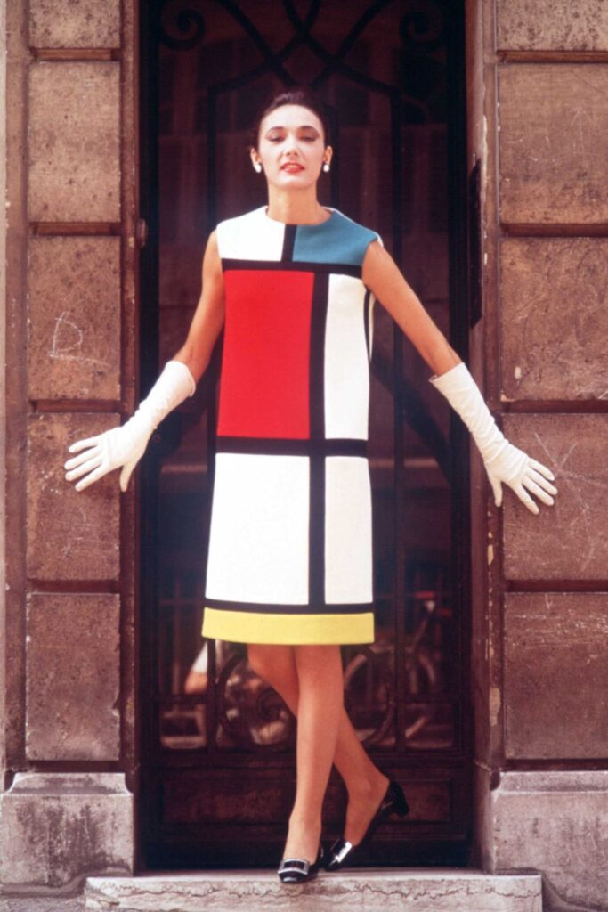 A colour photograph of a woman with brown hair standing in a doorway. Her dress, designed by Yves Saint Laurent, has am extremely straight cut and is patterned like a Mondrian painting, divided by black lines into squares which are white, blue or yellow. She is wearing white gloves and black pumps.