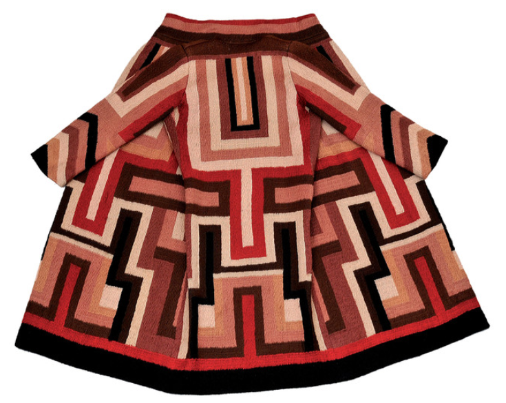 A coat, seen from the back with the sides opened out. It's long and the pattern is brown, black, creamy and red geometric patterns.