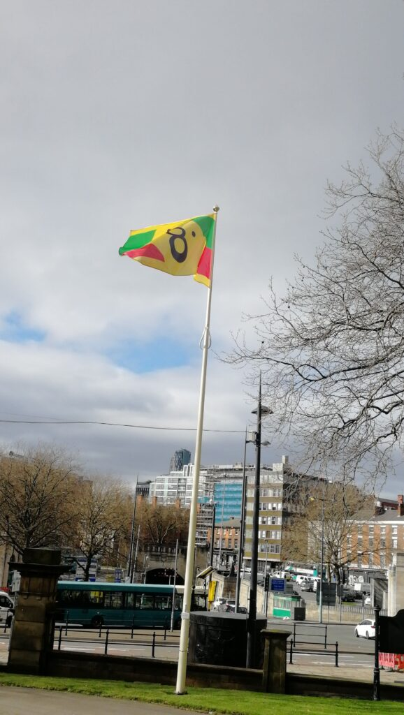 A flag flying in yellow, green and red against a city backdrop, with what appears to be a number 8.