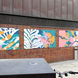 four mural panels on a brick wall, outside. Each panel is decorated with shapes of flora and fauna in pinks, yellows, greens, blues and white. It's outlines and silhouettes rather than details