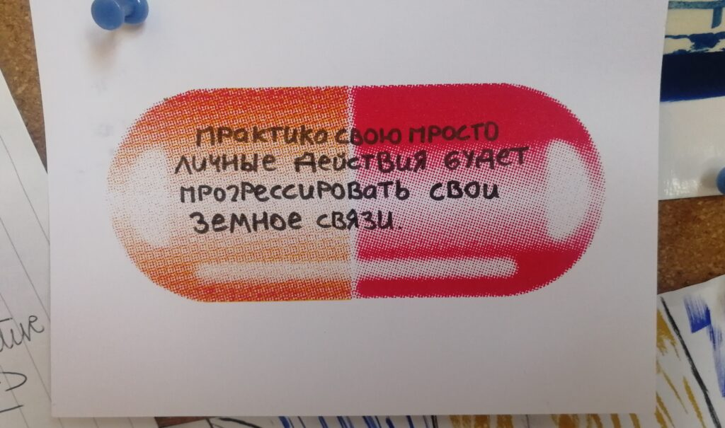 A postcard of a half red, half yellow pill with a Russian message written on it in black