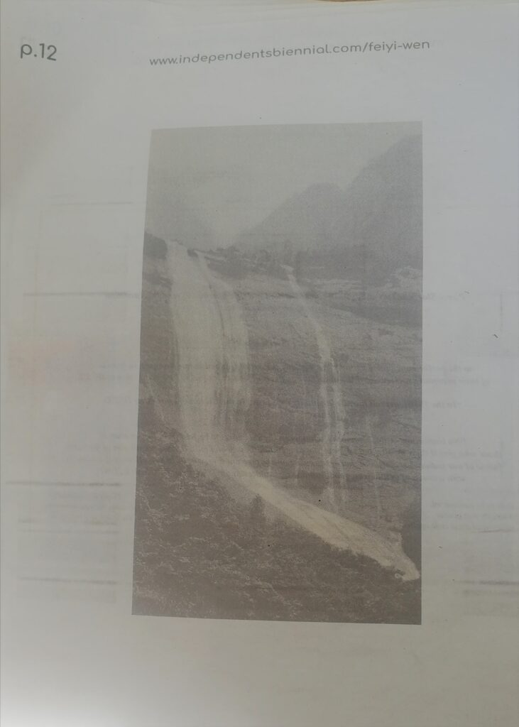 """A page of a newspaper-print type containing a light monochrome photographs of a waterfall. Reads """"pg 12"""" then a URL to the independents biennial website page for artist Feiyi Wen"""