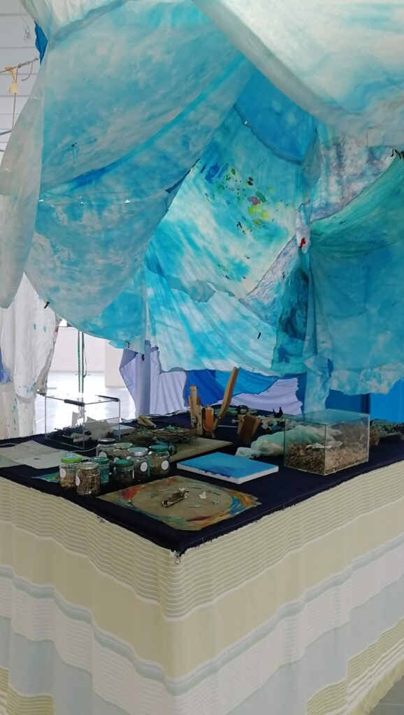 A table under a light blue tie-dyed textile