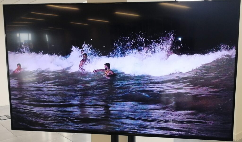 A TV screen with a show of south Asian men smiling as they are hit by a wave