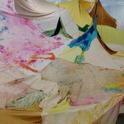 A series of textiles sewn together in different tie-dye colours and patterns