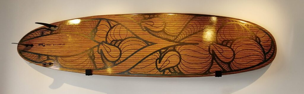 a wooden surfboard with black designs painted on